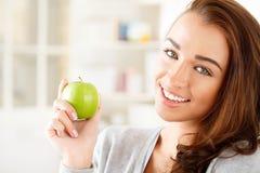 Recht gesunde junge Frau, die einen grünen Apfel anhalten lächelt Lizenzfreies Stockbild