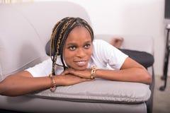 Recht glückliche Frau auf dem Sofa Stockfotos