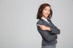 Recht glückliche Frau kreuzte Arme und das Zeigen weg auf copyspace lizenzfreie stockfotos