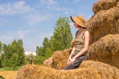 Recht glückliche Frau mit dem Hut, der auf Strohballen sitzt und etwas Rest erhält Lizenzfreie Stockfotografie
