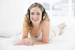 Recht glückliches blondes Lügen im Bett, das Musik hört Stockfoto