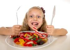 Recht glückliches kaukasisches weibliches Kind, das voll Teller der Süßigkeit in der gefährlichen Diät des süßen Zuckermissbrauch Lizenzfreie Stockbilder