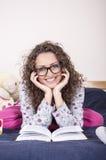 Recht glückliches Mädchen auf dem Bett Stockfotografie
