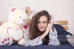 Recht glückliches Mädchen auf dem Bett Lizenzfreie Stockfotografie