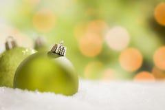 Recht grüne Weihnachtsverzierungen auf Schnee über einem abstrakten Hintergrund Stockbilder