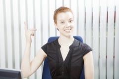Hübsche Geschäftsfrau, die über ihren Kopf zeigt Stockfotografie