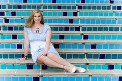 Recht jugendlich Mädchen, das auf eleganten blauen Schritten sitzt Lizenzfreie Stockfotografie