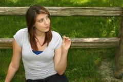 Recht jugendlich Mädchen, das draußen durch Zaun lächelt Lizenzfreie Stockbilder