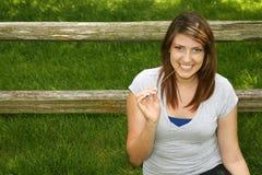 Recht jugendlich Mädchen, das draußen durch Zaun lächelt Stockbilder