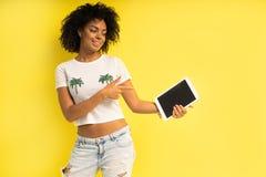 Recht junge afroe-amerikanisch Frauenstellung und mit Tablet-Computer lokalisiert über gelbem Hintergrund lizenzfreies stockbild
