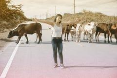 Recht junge Asiatin genießen Sommertag mit Kuh auf einer Straße Stockfotografie