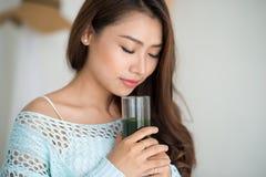 Recht junge asiatische Frau, die grünen Frischgemüsesaft trinkt oder Stockbilder