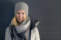 Recht junge blonde Frau in der modischen Winterausstattung Stockfotografie