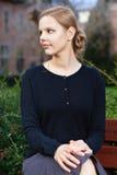 Recht junge blonde Frau, die auf Bank sitzt Stockbild