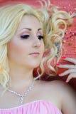 Recht junge blonde Frau, die auf dem Teppich mit farbigen Perlen sitzt Stockfoto