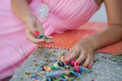 Recht junge blonde Frau, die auf dem Teppich mit farbigen Perlen sitzt Stockbilder
