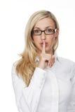 Recht junge blonde Frau, die an der Kamera zum Schweigen bringt Lizenzfreie Stockfotos