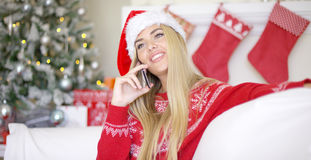 Recht junge blonde Frau, die an ihrem Handy plaudert Lizenzfreie Stockbilder