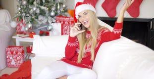Recht junge blonde Frau, die an ihrem Handy plaudert Lizenzfreies Stockbild