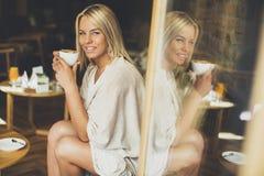 Recht junge blonde Frau, die im Café sitzt Lizenzfreie Stockfotografie