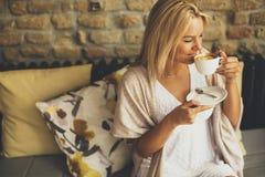Recht junge blonde Frau, die im Café sitzt Stockfotos