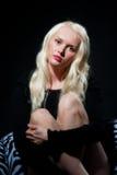 Recht junge blonde Frau im Schwarzen Stockfotos