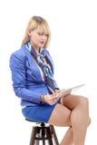 Recht junge blonde Frau mit der Tablette, sitzend auf einem Schemel Stockfotos