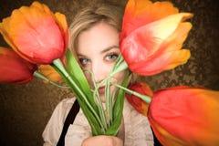 Recht junge blonde Frau mit Plastikblumen Stockbild