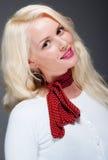 Recht junge blonde Frau mit rotem Schal Lizenzfreie Stockbilder