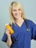 Recht junge blonde Gesundheitspflegefachmannpillen Lizenzfreie Stockfotografie