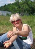 Recht junge blonde lächelnde tragende Sonnenbrille der Frau mit Ofenkartoffel in der Hand Stockfotos