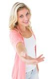 Recht junge Blondine, die ihre Hand anbietet Stockbild