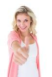 Recht junge Blondine, die sich Daumen zeigt Lizenzfreies Stockfoto