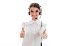 Recht junge BrunetteFernsprechamt-Arbeitskraftfrau mit Kopfhörern und Mikrofon lächelnd und Daumen oben auf Kamera zeigend Stockfoto