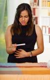 Recht junge Brunettefrau, die steht, hochhalten Schwangerschaftshaupttest in der Front, schauend betont, ihren eigenen Magen berü Stockfotografie