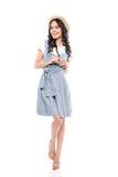 Recht junge Brunettefrau im Strohhut und im Kleid lächelnd an der Kamera Stockbild