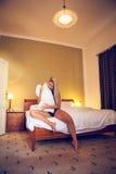 Recht junge Dame in der Liebe, die auf dem Bett und den Spielen mit einem Kissen sitzt Lizenzfreie Stockfotografie