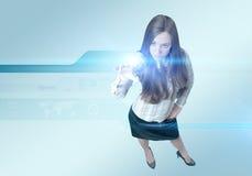 Recht junge Dame, die neue Technologien einsetzt stockfoto