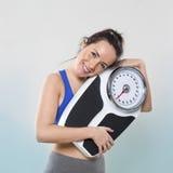 Recht junge Dame, die sie Skalen glücklich mit Gewicht hält Lizenzfreie Stockfotos