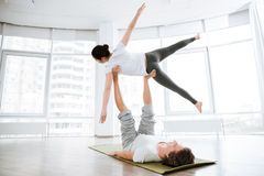 Recht junge Frau übendes acro Yoga mit Partner Lizenzfreies Stockbild