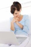 Recht junge Frau auf Couch unter Verwendung des Laptops Stockbild