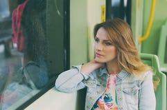 Recht junge Frau auf einer Straßenbahn/einer Straßenbahn, während sie touristisch Stockfotografie
