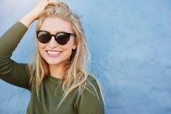 Recht junge Frau beim Sonnenbrillelächeln