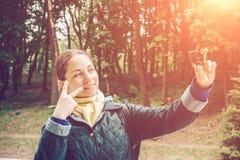 Recht junge Frau Blogger nimmt selfie Porträt an der Aktionskamera und Showfrieden singen durch Finger Stockfotos