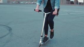 Recht junge Frau in den Jeans tragen, wenn das sehr lange Haar den Roller reitet Spielerische Stimmung, Kindheitsspaß Städtische  stock footage