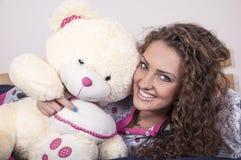 Recht junge Frau in den Pyjamas mit Teddybären Stockfotografie