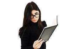 Recht junge Frau, die über der Spitze ihrer Gläser schaut Lizenzfreie Stockbilder