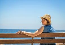 Recht junge Frau, die allein auf einer Bank vor dem Meer sitzt lizenzfreie stockfotos