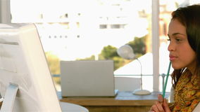 Recht junge Frau, die auf Computermonitor sich konzentriert und mit einem Bleistift spielt stock video footage