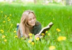 Recht junge Frau, die auf dem Gras mit Löwenzahn ein Buch lesend liegt Lizenzfreies Stockfoto